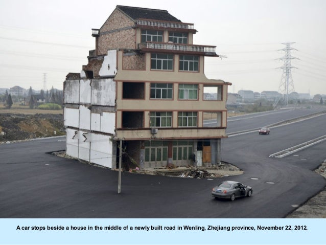 A car stops beside a house in the middle of a newly built road in Wenling, Zhejiang province, November 22, 2012.