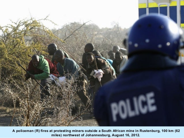 A policeman (R) fires at protesting miners outside a South African mine in Rustenburg, 100 km (62                       mi...