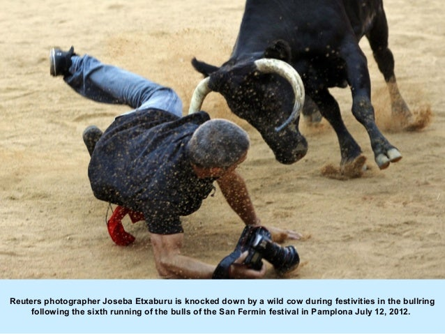 Reuters photographer Joseba Etxaburu is knocked down by a wild cow during festivities in the bullring     following the si...