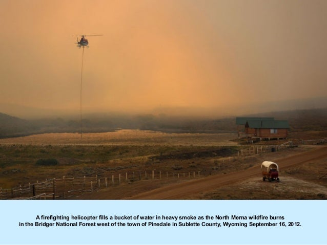 A firefighting helicopter fills a bucket of water in heavy smoke as the North Merna wildfire burnsin the Bridger National ...