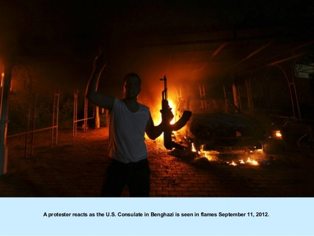 A protester reacts as the U.S. Consulate in Benghazi is seen in flames September 11, 2012.