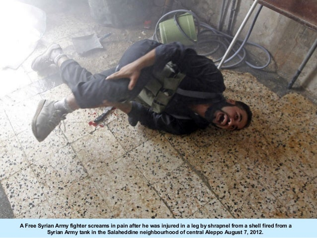 A Free Syrian Army fighter screams in pain after he was injured in a leg by shrapnel from a shell fired from a           S...