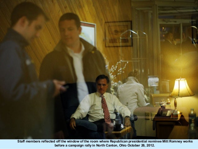 Staff members reflected off the window of the room where Republican presidential nominee Mitt Romney works                ...