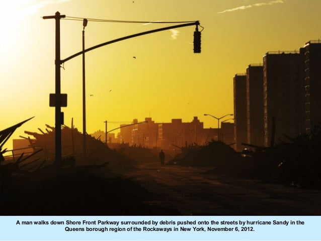 A man walks down Shore Front Parkway surrounded by debris pushed onto the streets by hurricane Sandy in the               ...