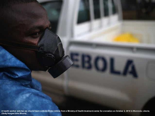 A health worker watches as a burial team collects Ebola victims from a Ministry of Health treatment center for cremation o...