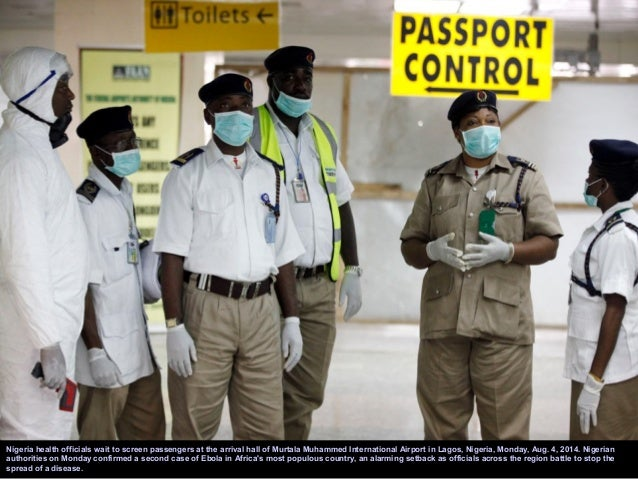 Members of Doctors Without Borders (MSF) wearing protective gear walk outside the isolation ward of the Donka Hospital, on...
