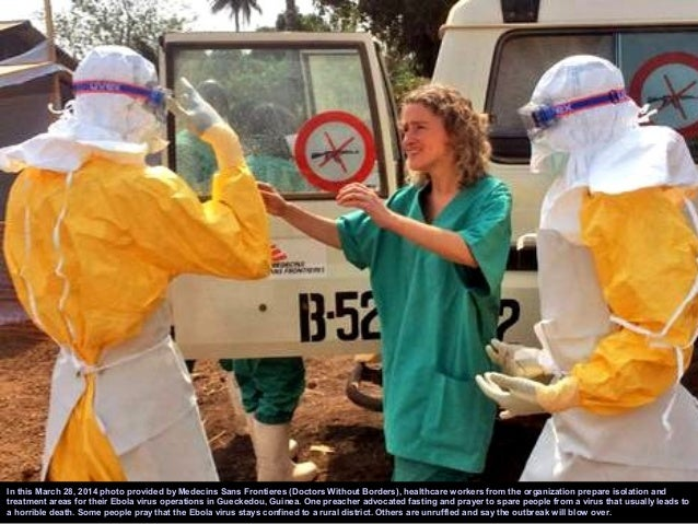 Volunteers prepare to remove the bodies of people who were suspected of contracting Ebola and died in the community in the...