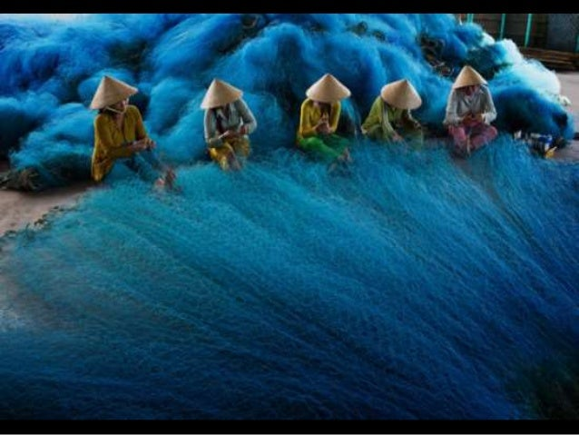 A group of women weave a fishing net in the Mekong Delta, Vietnam, in preparation for the annual flooding of the river and...