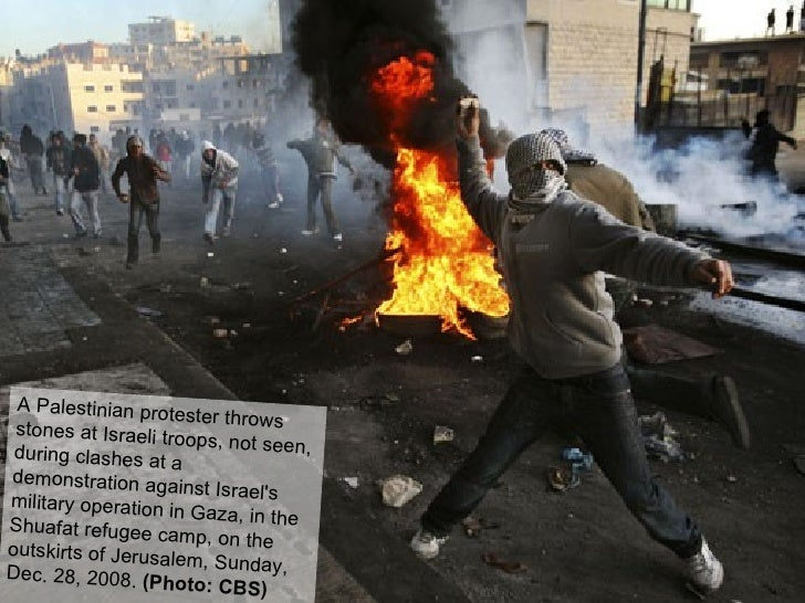 A Palestinian protester throws stones at Israeli troops, not seen, during clashes at a demonstration against Israel's mili...