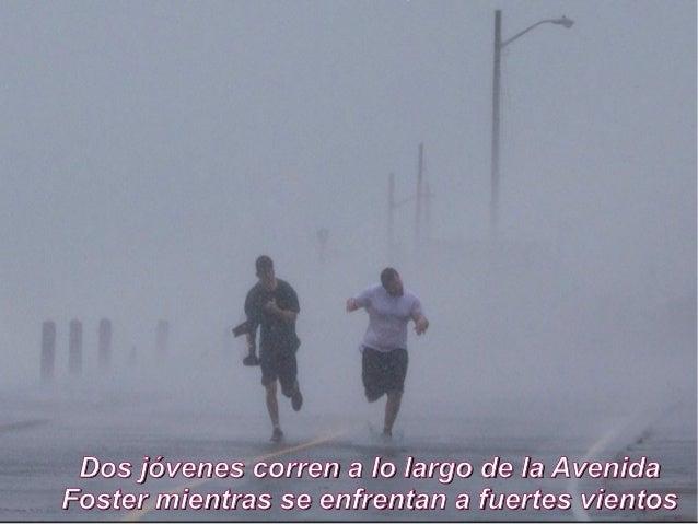 Dos jóvenes corren a lo largo de la AvenidaFoster mientras se enfrentan a fuertes vientos