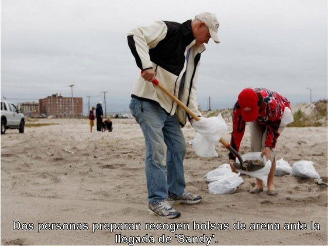 Dos personas preparan recogen bolsas de arena ante la                 llegada de Sandy.