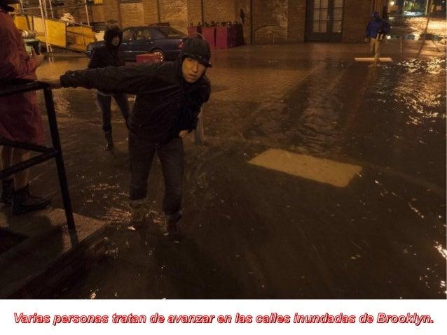 Varias personas tratan de avanzar en las calles inundadas de Brooklyn.
