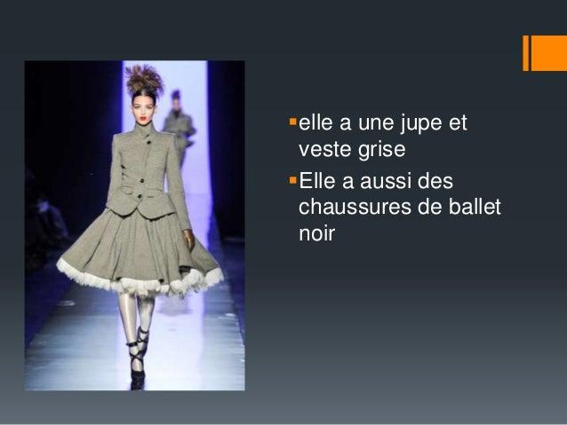 elle a une jupe et  veste grise  Elle a aussi des  chaussures de ballet  noir