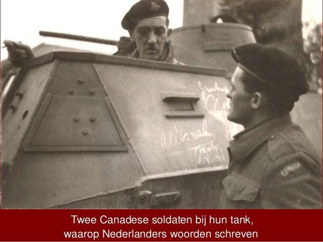 Twee Canadese soldaten bij hun tank, waarop Nederlanders woorden schreven