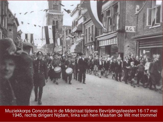 Muziekkorps Concordia in de Midstraat tijdens Bevrijdingsfeesten 16-17 mei 1945, rechts dirigent Nijdam, links van hem Maa...