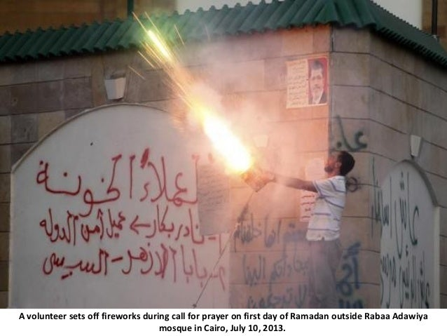 A volunteer sets off fireworks during call for prayer on first day of Ramadan outside Rabaa Adawiya mosque in Cairo, July ...