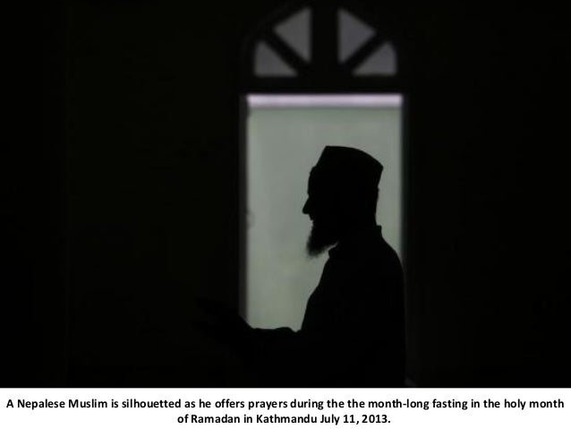 A Nepalese Muslim is silhouetted as he offers prayers during the the month-long fasting in the holy month of Ramadan in Ka...