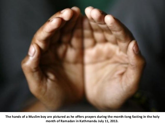 The hands of a Muslim boy are pictured as he offers prayers during the month-long fasting in the holy month of Ramadan in ...