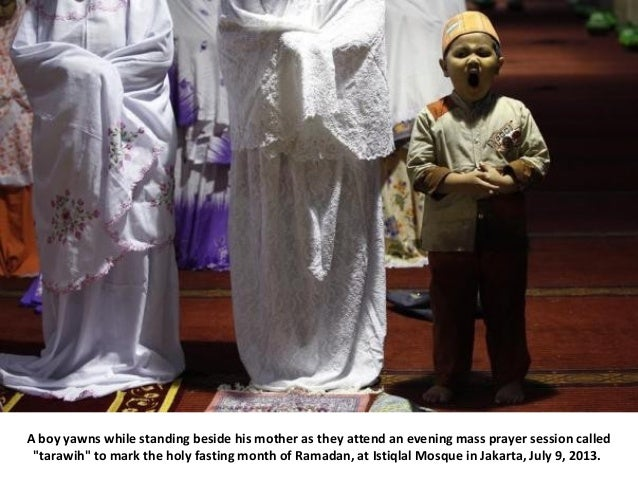 """A boy yawns while standing beside his mother as they attend an evening mass prayer session called """"tarawih"""" to mark the ho..."""
