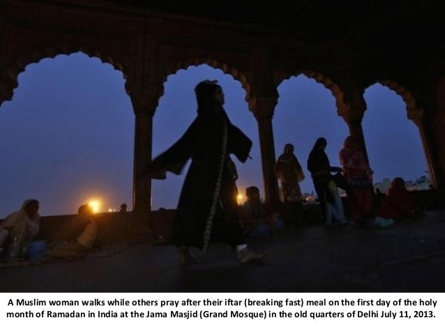 A Muslim woman walks while others pray after their iftar (breaking fast) meal on the first day of the holy month of Ramada...