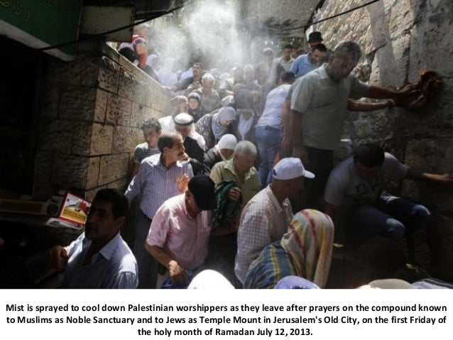 Mist is sprayed to cool down Palestinian worshippers as they leave after prayers on the compound known to Muslims as Noble...