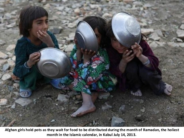 Afghan girls hold pots as they wait for food to be distributed during the month of Ramadan, the holiest month in the Islam...
