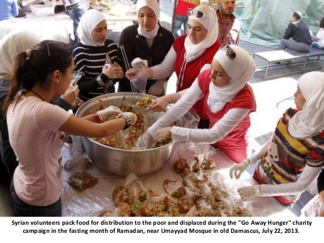 """Syrian volunteers pack food for distribution to the poor and displaced during the """"Go Away Hunger"""" charity campaign in the..."""