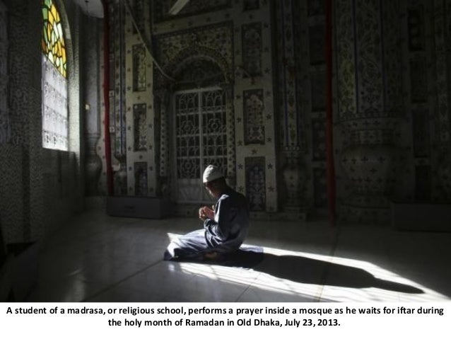 A student of a madrasa, or religious school, performs a prayer inside a mosque as he waits for iftar during the holy month...