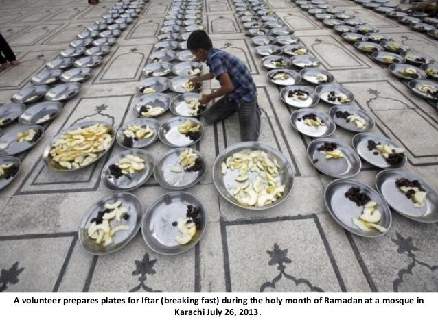 A volunteer prepares plates for Iftar (breaking fast) during the holy month of Ramadan at a mosque in Karachi July 26, 201...