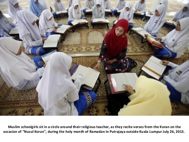 Muslim schoolgirls sit in a circle around their religious teacher, as they recite verses from the Koran on the occasion of...