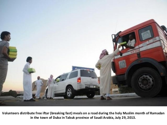 Volunteers distribute free iftar (breaking fast) meals on a road during the holy Muslim month of Ramadan in the town of Du...
