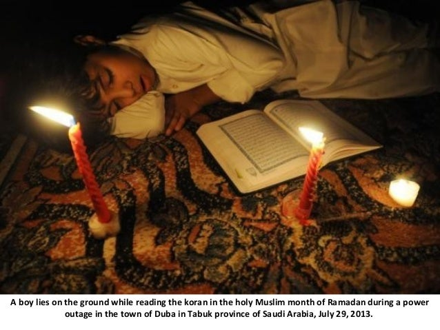 A boy lies on the ground while reading the koran in the holy Muslim month of Ramadan during a power outage in the town of ...