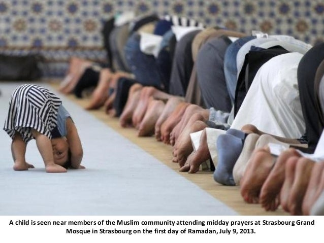 A child is seen near members of the Muslim community attending midday prayers at Strasbourg Grand Mosque in Strasbourg on ...