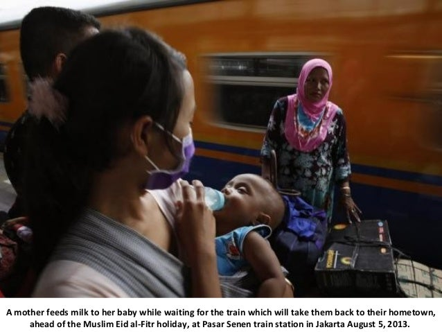 A mother feeds milk to her baby while waiting for the train which will take them back to their hometown, ahead of the Musl...
