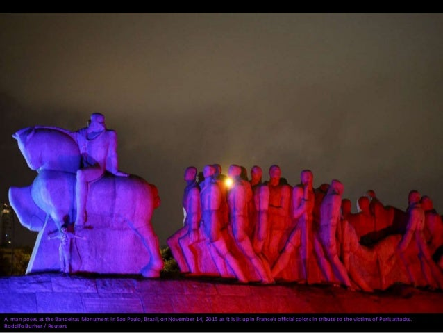 A man poses at the Bandeiras Monument in Sao Paulo, Brazil, on November 14, 2015 as it is lit up in France's official colo...