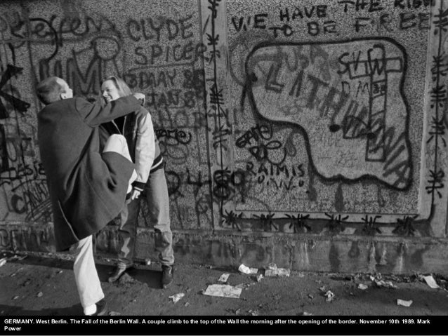 GERMANY. West Berlin. The Fall of the Berlin Wall. A couple climb to the top of the Wall the morning after the opening of ...