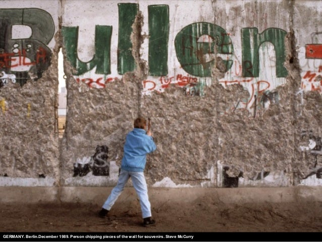 GERMANY. Berlin.December 1989. Person chipping pieces of the wall for souvenirs. Steve McCurry