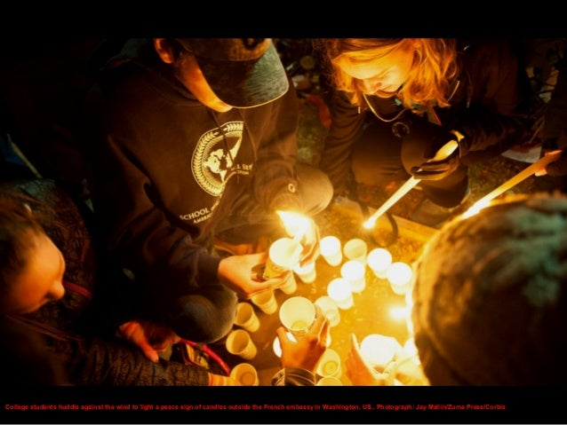 People light candles and lay flowers at the French embassy in Warsaw, Poland.. Photograph: Kacper Pempel/Reuters