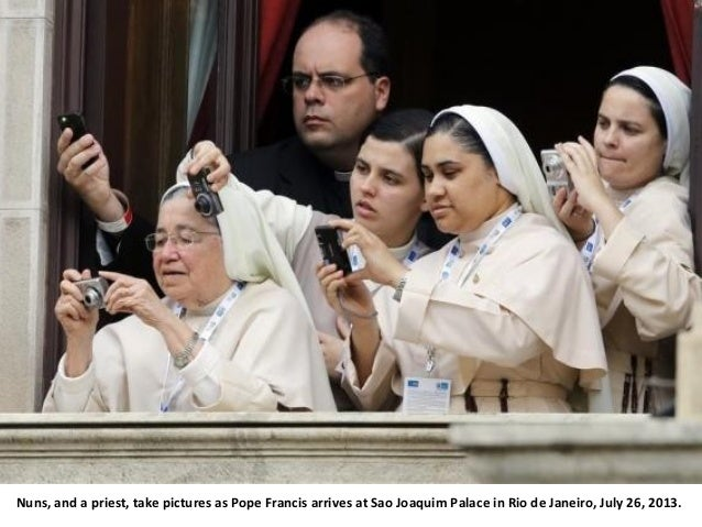 Nuns, and a priest, take pictures as Pope Francis arrives at Sao Joaquim Palace in Rio de Janeiro, July 26, 2013.