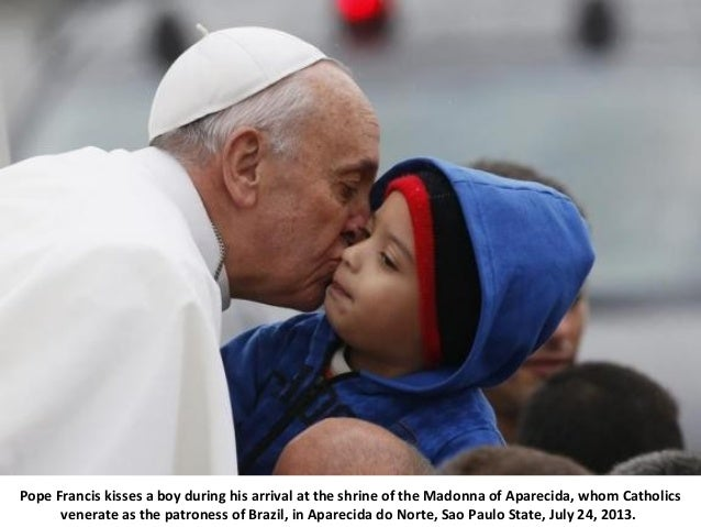 Pope Francis kisses a boy during his arrival at the shrine of the Madonna of Aparecida, whom Catholics venerate as the pat...