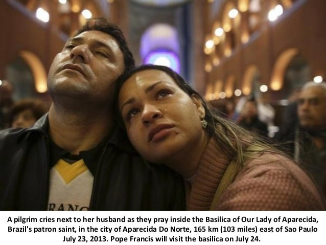 A pilgrim cries next to her husband as they pray inside the Basilica of Our Lady of Aparecida, Brazil's patron saint, in t...