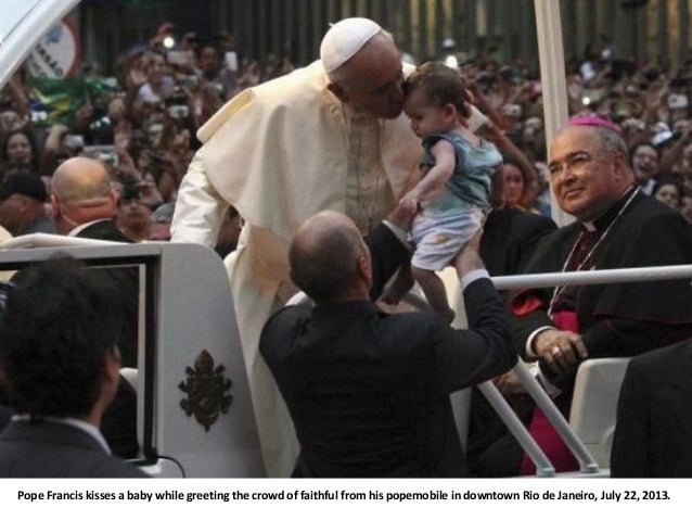 Pope Francis kisses a baby while greeting the crowd of faithful from his popemobile in downtown Rio de Janeiro, July 22, 2...