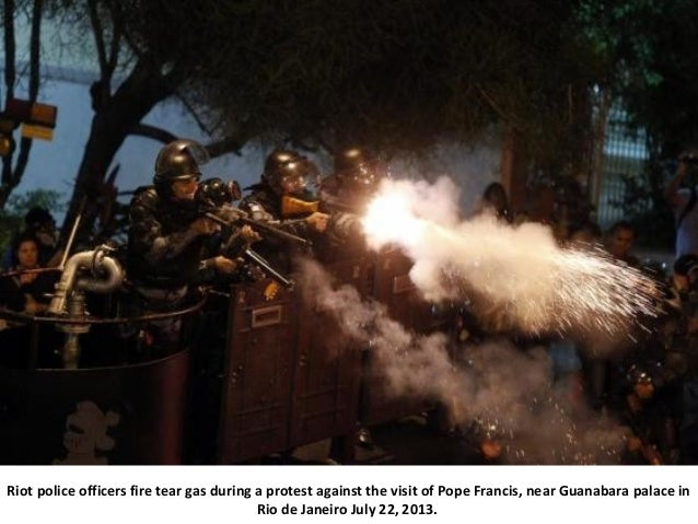 Riot police officers fire tear gas during a protest against the visit of Pope Francis, near Guanabara palace in Rio de Jan...