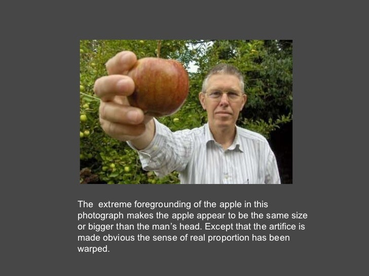 The  extreme foregrounding of the apple in this photograph makes the apple appear to be the same size or bigger than the m...