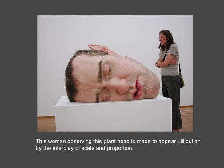 This woman observing this giant head is made to appear Lilliputian by the interplay of scale and proportion.