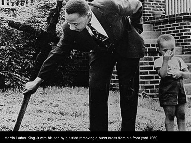 Martin Luther King Jr with his son by his side removing a burnt cross from his front yard 1960