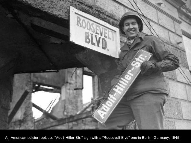 """An American soldier replaces """"Adolf-Hitler-Str."""" sign with a """"Roosevelt Blvd"""" one in Berlin, Germany, 1945."""