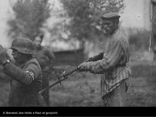 A liberated Jew holds a Nazi at gunpoint.