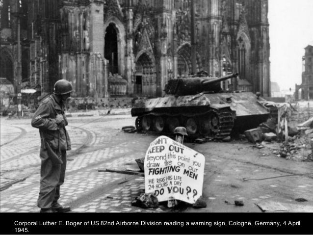 Corporal Luther E. Boger of US 82nd Airborne Division reading a warning sign, Cologne, Germany, 4 April 1945.