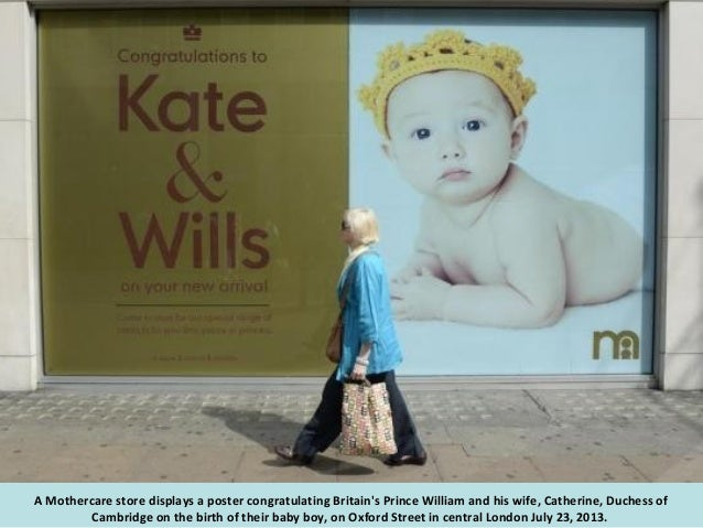 Employees Amy Meenagh (R) and Amy Bush hang a sign celebrating the news that Catherine, Duchess of Cambridge, has given bi...
